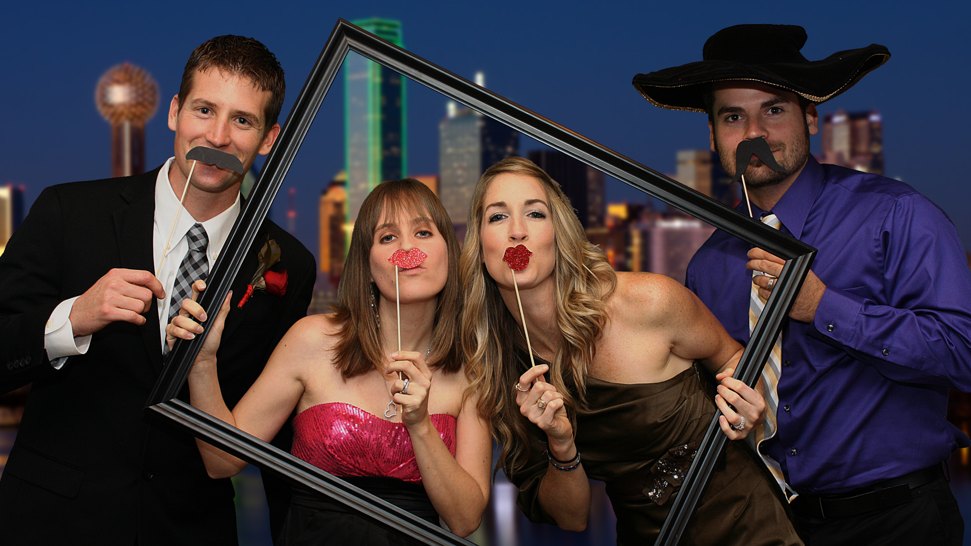 Friends pose for photography at a wedding in a digital sharing photosation. They are seen inside a picture frame with a green screen image of Dallas in the background.
