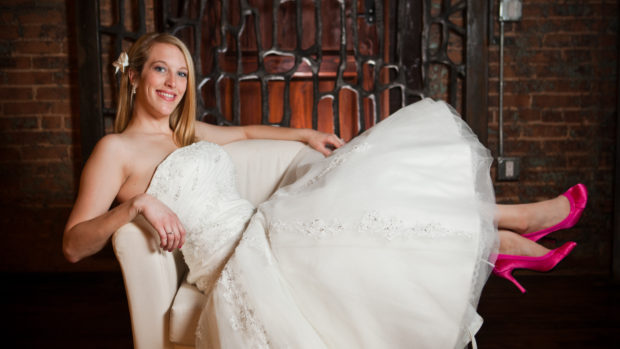 bride christine posed in a chair in wedding dress with bright pink high heels