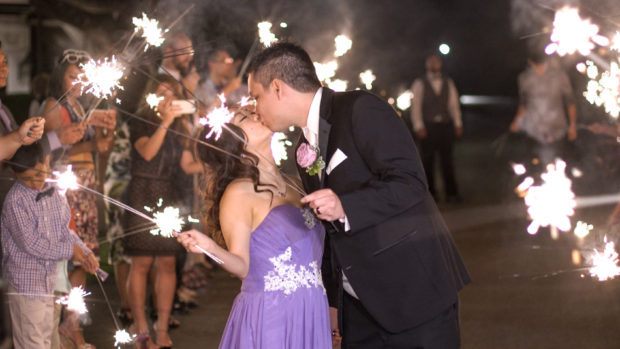 Sparklers burn as a bride and groom exit their wedding reception in Dallas, tx