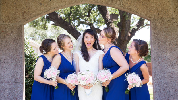 Bride, Milena, poses with her bridesmaids for wedding photographer at the bell tower chapel in Fort Worth, TX