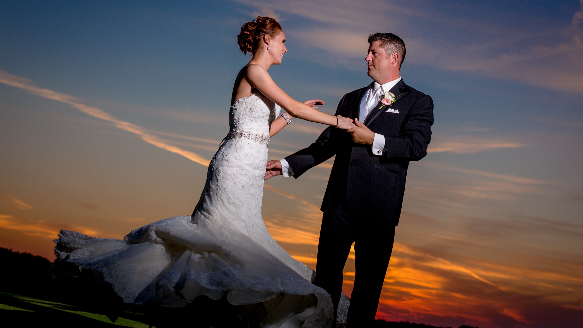 Dallas wedding video still frame of a groom spinning his bride in the sunset.